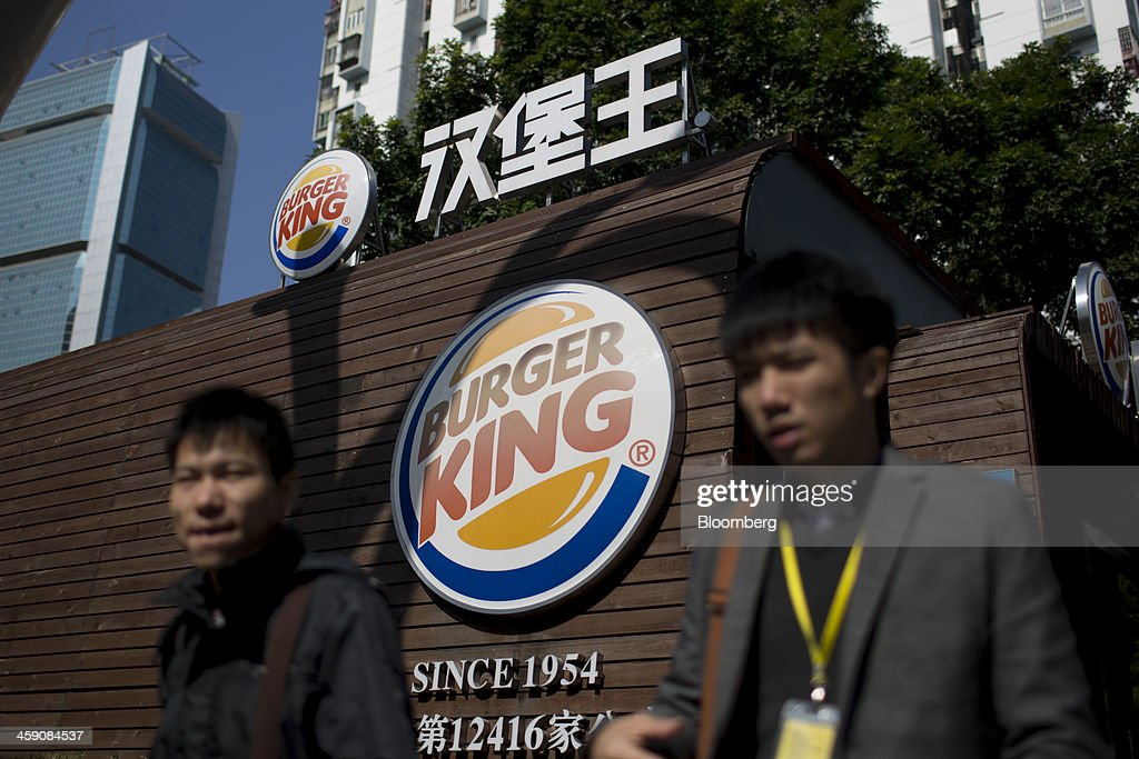 Men walk past a Burger King Worldwide Inc. store in the Luohu district of Shenzhen, China, on Thursday, Dec. 19, 2013. Two of Chinas three biggest securities firms predict the central bank will refrain from using open-market operations to inject funds this week as policy makers seek to rein in debt and contain inflation. Photographer: Brent Lewin/Bloomberg via Getty Images