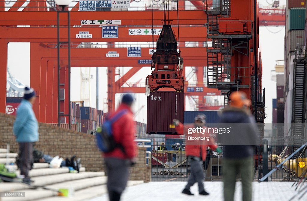 Men walk past a container as it is unloaded from a vessel at a shipping terminal in Tokyo, Japan, on Wednesday, Jan. 23, 2013. Japan's exports fell more than analysts forecast and the annual trade deficit swelled to a record, bolstering the case for Prime Minister Shinzo Abe to weaken the yen even as trade tensions mount. Photographer: Tomohiro Ohsumi/Bloomberg via Getty Images