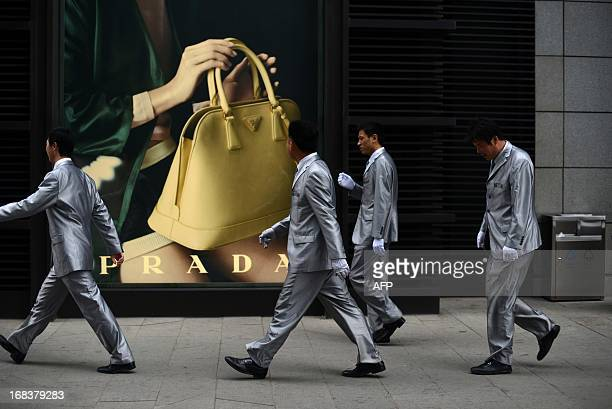 Men walk past a luxury advertising billboard outside a mall in Beijing on May 9 2013 Inflation in China accelerated to 24 percent yearonyear in April...