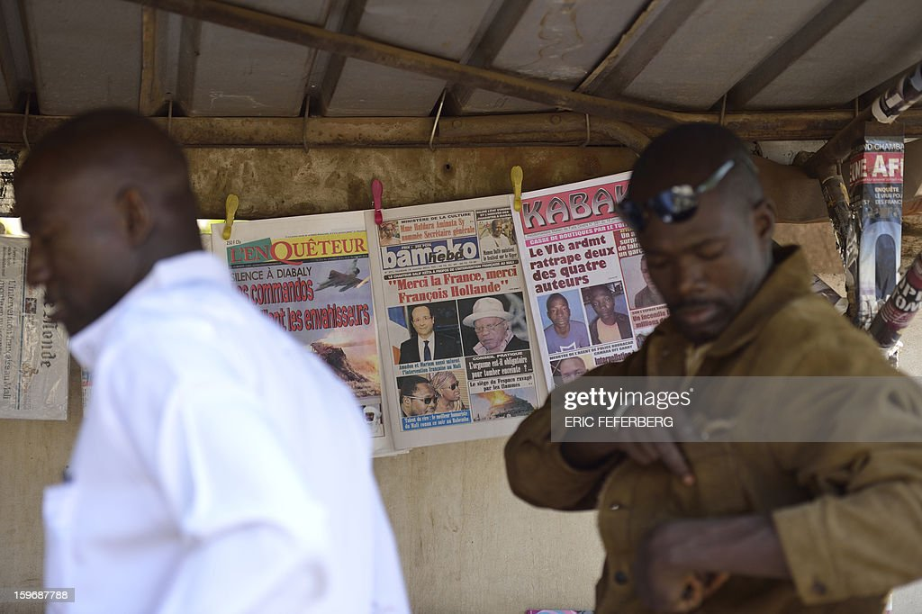 Men walk past a newspapers stand on January 18, 2013 in a street of Bamako. French Foreign Minister Laurent Fabius said he would attend an emergency summit of the west African bloc ECOWAS on Saturday to help accelerate the deployment of an African military force in Mali. AFP PHOTO / ERIC FEFERBERG