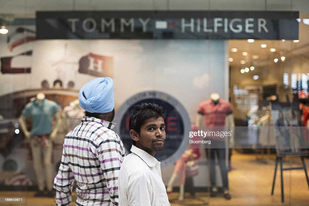 Men walk past a Tommy Hilfiger store at the AlphaOne shopping mall in Amritsar, India, on Thursday, May 9, 2013. India's consumer price index (CPI) for April rose 9.39 percent year on year, the Central Statistics Office said in a statement on its website. Photographer: Brent Lewin/Bloomberg via Getty Images