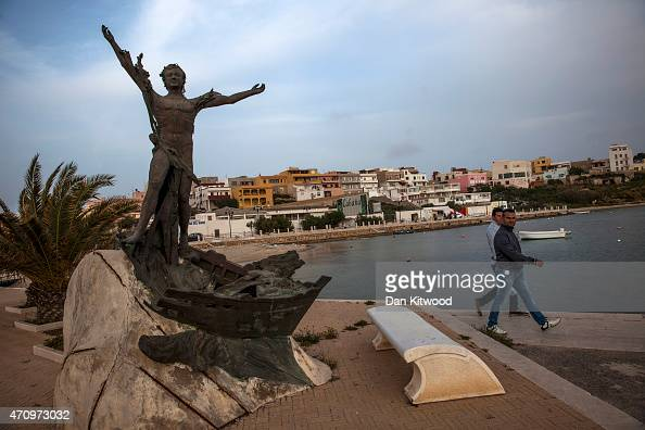 Men walk past an iron statue of a man standing above the wreckage of a boat on the harbour on April 24 2015 in Lampedusa Italy Migrants continue to...