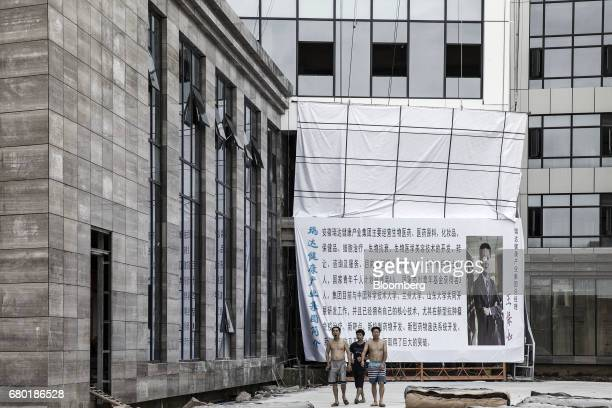 Men walk past an under construction hospital inside the Hainan Boao Lecheng InternationalMedicalTourismPilotZone in Boao China on Saturday March...