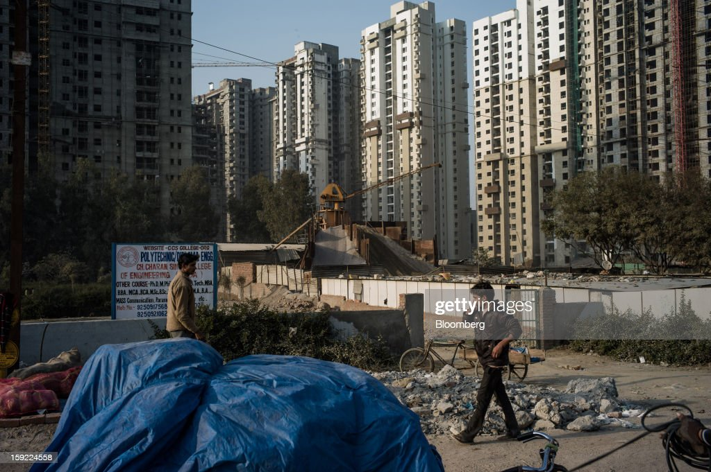 Men walk past apartment blocks under construction in Noida, Uttar Pradesh, India, on Wednesday, Jan. 9, 2013. India's Finance Ministry predicts GDP growth of as little as 5.7 percent in the year to March 31, the least in a decade. Photographer: Sanjit Das/Bloomberg via Getty Images