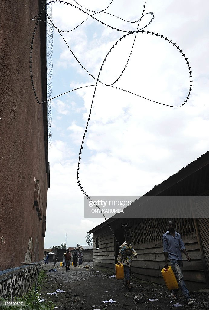 Men walk past barbed wire used to secure the yard of Muzenze prison on November 21, 2012 as it hangs off the perimeter walls of the main jail house in Goma. Almost all inmates of Goma's main prison managed to break out after prison warders abandoned their positions to flee from advancing M23 rebels two days ago. The M23 rebel group in the Democratic Republic of Congo, which says it now controls all of Goma and nearby crossing points on the border with Rwanda vowed today it would not stop at Goma, after seizing the key eastern city this week. A spokesman for the M23 rebel group in the Democratic Republic of Congo called Wednesday for President Joseph Kabila to step down, saying he was not the legitimate winner of elections last year. AFP PHOTO/Tony KARUMBA