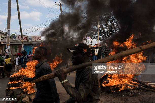 Men walk past burning tires during a protest in Kibera Kenya's biggest slum on August 9 2017 in Nairobi Kenya The protest started after police...
