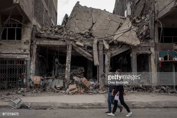 Men walk past destroyed buildings on November 6 2017 in Mosul Iraq Five months after Mosul Iraq's secondlargest city was liberated from ISIL in a...