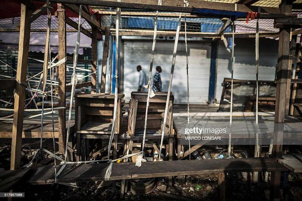 Men walk past empty stalls and closed shops during a 'dead city' strike called by five defeated opposition candidates to protest the reelection of...
