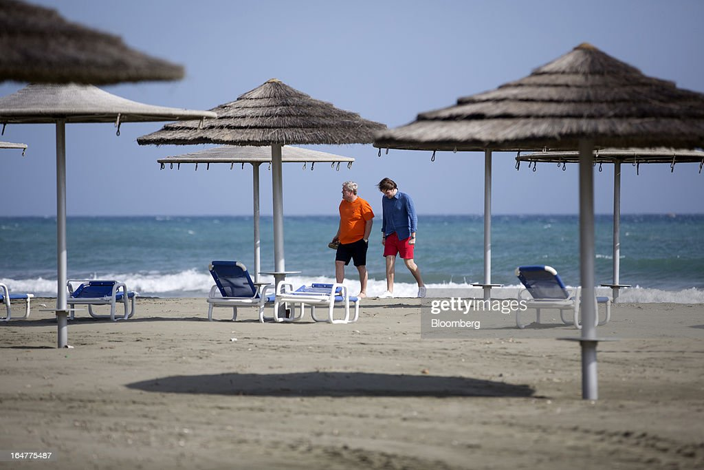 Men walk past sunloungers on the private beach at St Raphael resort hotel in Limassol, Cyprus, on Wednesday, March 27, 2013. Directly or indirectly, tourism makes up a quarter of Cyprus's economy with visitors from the two main tourism markets, Germany and U.K. Photographer: Simon Dawson/Bloomberg
