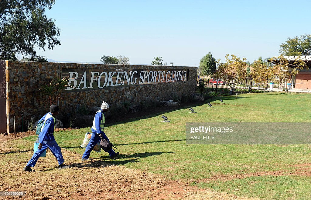 Men walk past the entrance to the Bafokeng Sports Campus near Rustenburg, on June 2, 2010 on the eve of the English football team arrives to stay and train ahead of their opening game against USA on June 12 during 2010 Soccer World Cup.