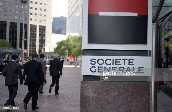 Men walk past the logo of the French bank Societe Generale located in front of its headquarters in the Paris business district of La Defense on...