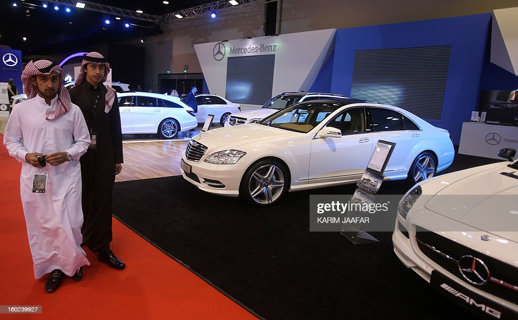 Men walk past the Mercedes-Benz stand during the third International Qatar Auto Show on January 28, 2013 in Doha. AFP PHOTO / AL-WATAN DOHA / KARIM JAAFAR == QATAR OUT ==