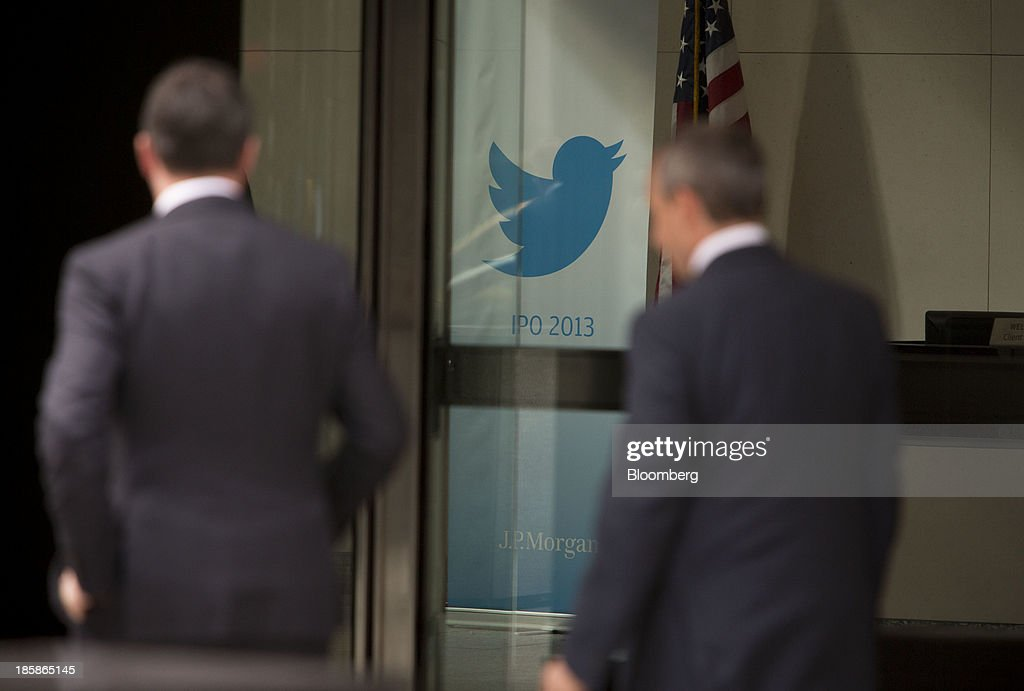 Men walk past the Twitter Inc. logo displayed in the lobby of JPMorgan Chase & Co. headquarters in New York, U.S., on Friday, Oct. 25, 2013. Twitter Inc. will make the case to potential investors in its initial public offering that it needs to keep spending to grow, and profit will come once it can reap the benefits of those investments. Photographer: Scott Eells/Bloomberg via Getty Images