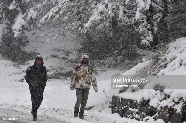 Men walk through a snowcovered Gulmarg Tangmarg Road on December 11 2017 about 38 kilometers from Srinagar India