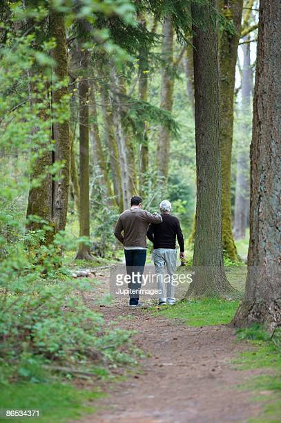 Men walking along a wooded pathway
