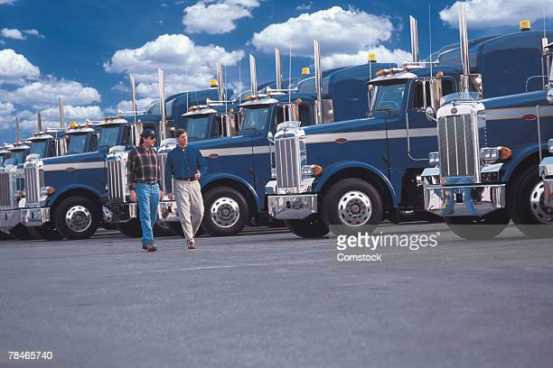 Men walking by row of semi trucks