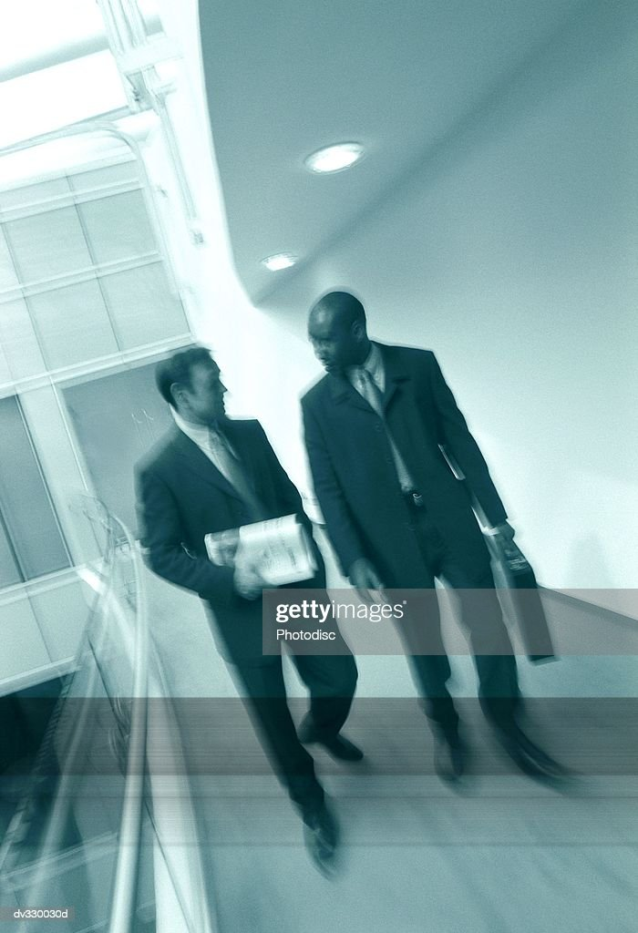 Men walking down office corridor : Stock Photo