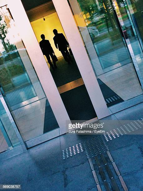 Men Walking In Building Seen Through Doorway