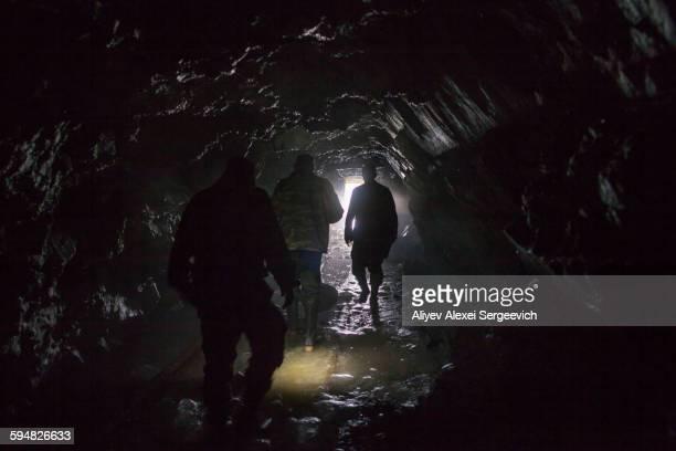 Men walking in dark cave