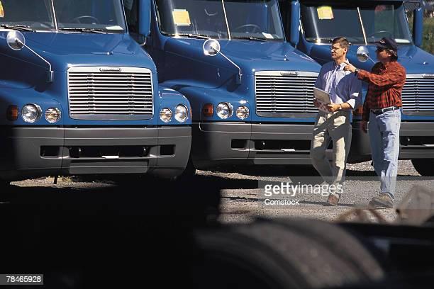 Men walking in front of parked semi trucks