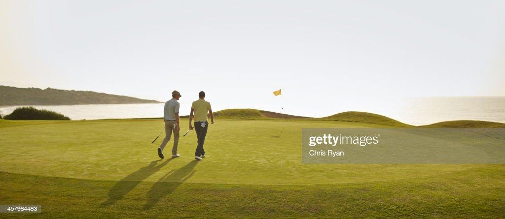 Men walking on golf course : Stock Photo