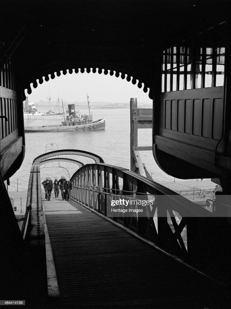 Men walking up a wooden bridge on a river c1945c1965