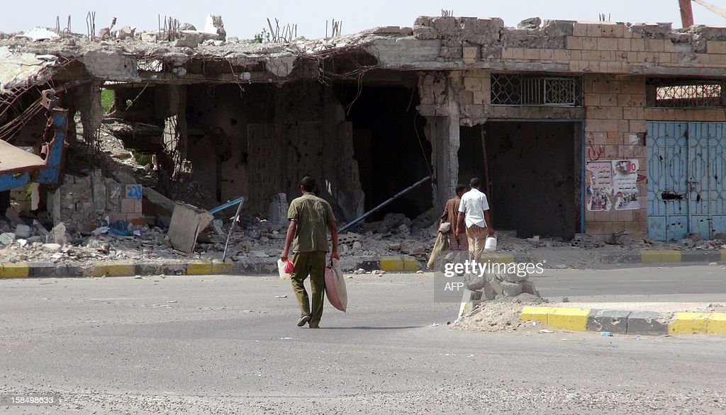 Men walks past destroyed buildings in Zinjibar, capital of Abyan province in southern Yemen on December 5, 2012, six months after the Yemeni army ousted al-Qaeda loyalists from the region. Before a counter-offensive by the army earlier this year, Al-Qaeda held large swathes of southern Yemen. But since its loss of a string of towns near the port city of Aden in June, most have fled into desert regions farther east. Although weakened, they continue to launch hit-and-run attacks on government and civilian targets across Yemen. AFP PHOTO/SAMI AL-ANSI