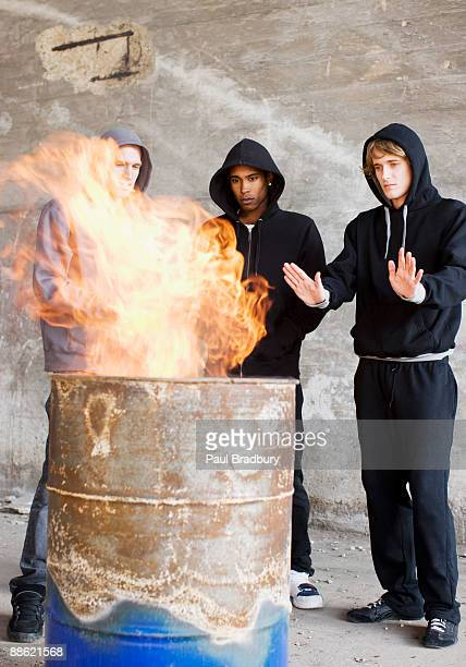 Men warming hands at fire in barrel