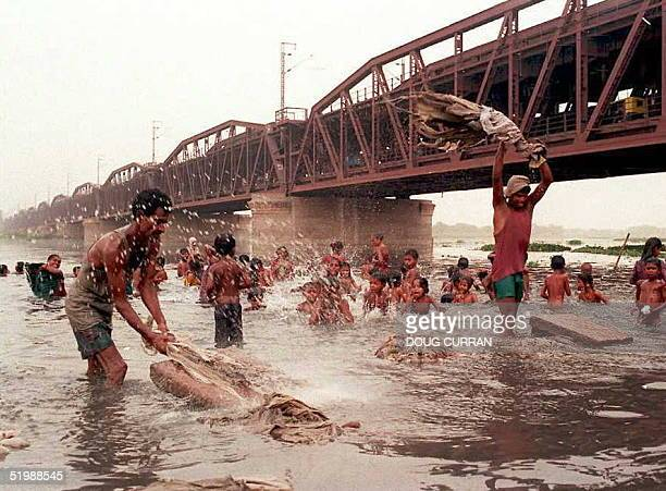 Men wash laundry by slamming the washing on slabs of stone as children play in the cool waters of the sacred Yamuna River beneath the Purana Bridge...