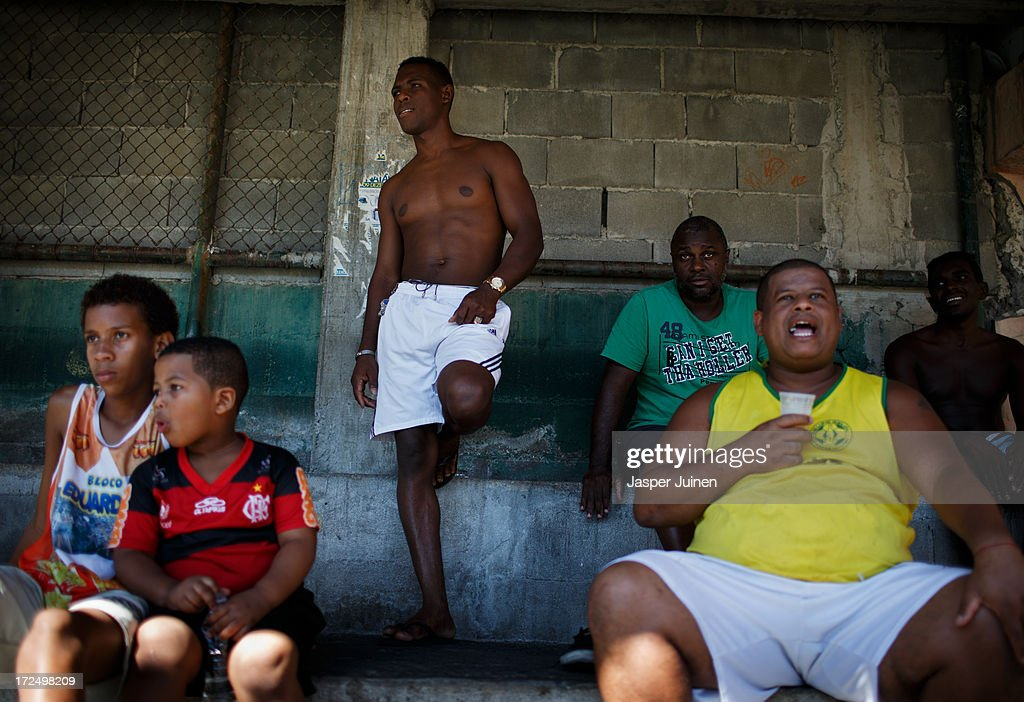 Men watch a game of football at the Complexo do Alemao favela on June 29, 2013 in Rio de Janeiro, Brazil. It was at the end of 2010 that under the stage of pacification some 300 police officers went into the Complexo do Alemao with tanks and helicopters to drive out the criminal gangs to establish a permanent police presences and to set up social services such as schools, healthcare centers, and rubbish collection. The Complexo do Alemao favela is, with a population of 100, 000 and stretching for more than 3 kilometers with a maze of narrow alleys and stairways, one of the largest favelas in Rio de Janeiro.
