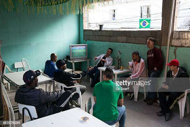 Men watch a television showing a World Cup match in a house in the poor neighbourhood of Itaquera adjacent to the 'Arena de Sao Paulo' stadium on...