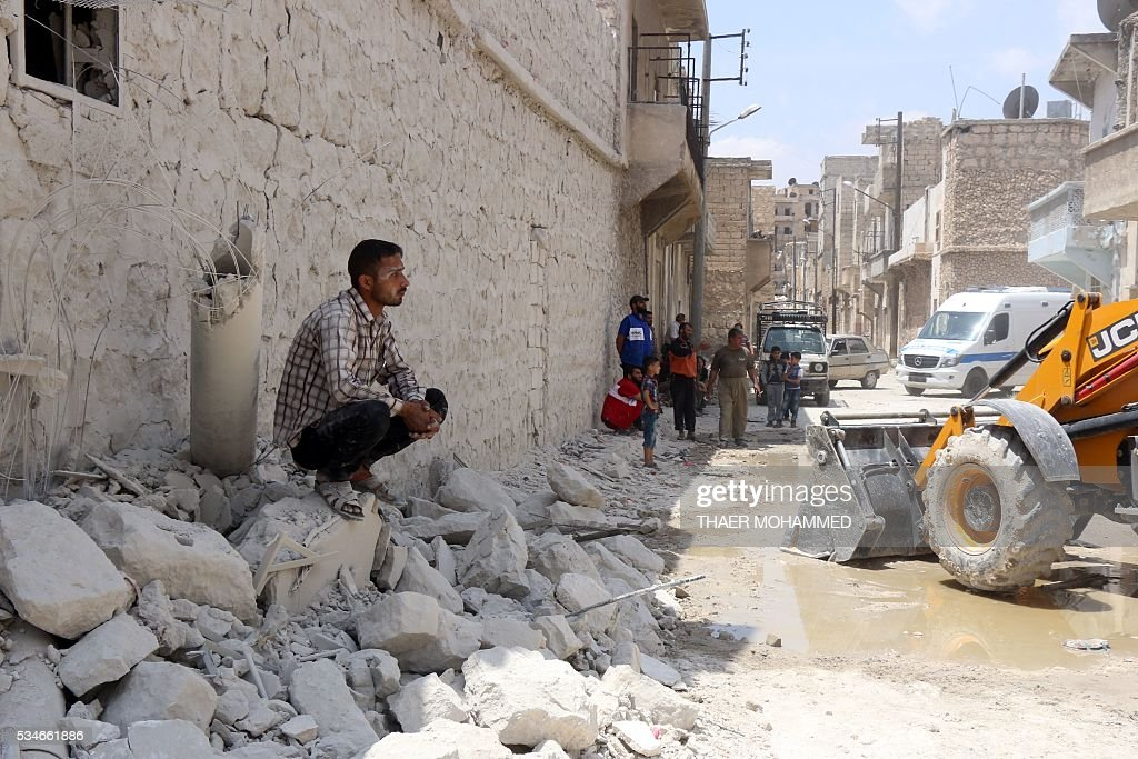 Men watch as an excavator clears debris of a building following a reported attack by Syrian government forces on May 27, 2016, in the Tariq al-Bab neighbourhood in the northern city of Aleppo. / AFP / THAER