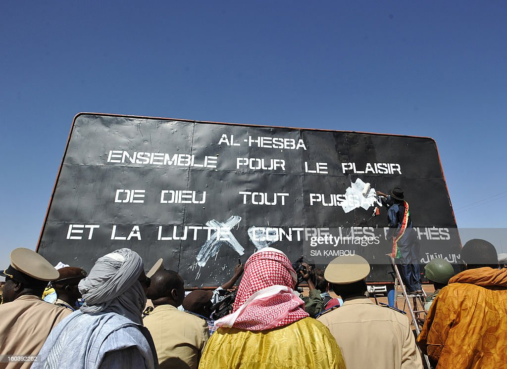 Men watch on January 30, 2013 the mayor of the northern Malian city of Gao, Sadou Harouna Diallo, cover with paint a billboard left by the Movement for Oneness and Jihad in West Africa (MUJAO), an offshoot of Al Qaeda in the Islamic Maghreb (AQIM). Gao was a key Islamist stronghold until it was retaken on January 26 by French and Malian troops in a major boost to the French-led offensive against the Al Qaeda-linked rebels, who have been holding Mali's vast desert north since last April. French troops on January 30 entered Kidal, the last Islamist bastion in Mali's north after a whirlwind Paris-led offensive, as France urged peace talks to douse ethnic tensions targeting Arabs and Tuaregs. Billboard reads: 'Al Hesbah, together for the pleasure of God almighty and the struggle against sins.'