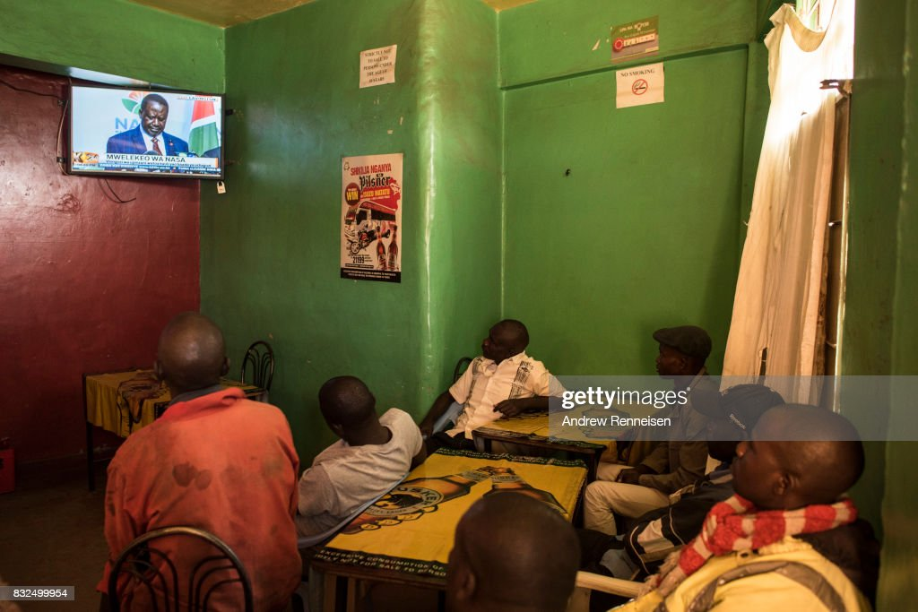 Men watch opposition candidate Raila Odinga speak at a press conference in a bar in the Mathare North neighborhood, on August 16, 2017 in Nairobi, Kenya. Odinga continued to reject the election results as he told his supporters that he would take the results to court and to demonstrate peacefully.