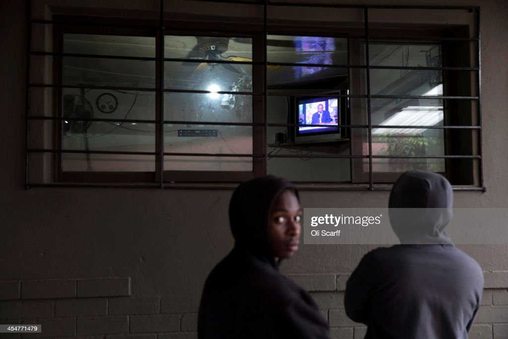 Men watch the official memorial service for Nelson Mandela on a television inside the Carpet House bar in Alexandra Township on December 10, 2013 in Johannesburg, South Africa. Over 60 heads of state have travelled to South Africa to attend a week of events commemorating the life of former South African President Nelson Mandela. Mr Mandela passed away on the evening of December 5, 2013 at his home in Houghton at the age of 95. Mandela became South Africa's first black president in 1994 after spending 27 years in jail for his activism against apartheid in a racially-divided South Africa.