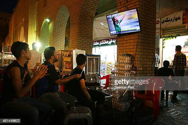Men watch the World Cup at a tea shop near the Citadel in Erbil on June 29 2014 in Erbil Iraq Tens of thousands of displaced Iraqis and Syrians have...