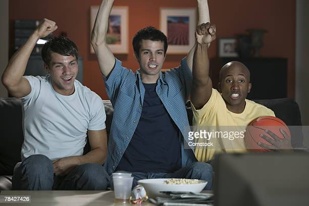 Men watching basketball game and cheering