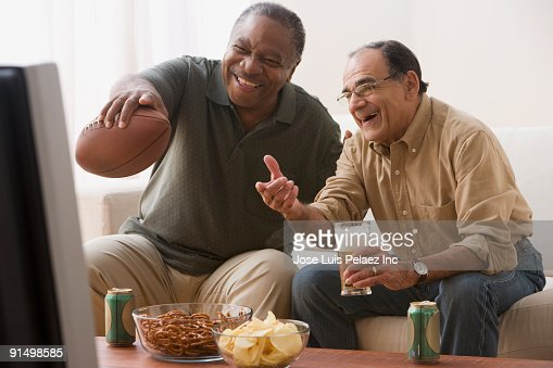 men watching football game in living room snacks stock photo similar images