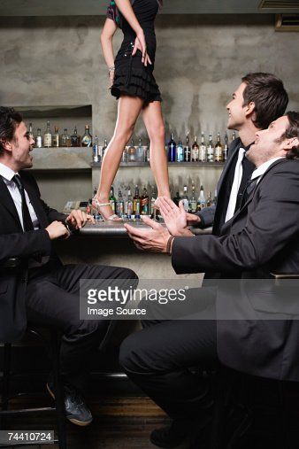 Men watching women walk on bar
