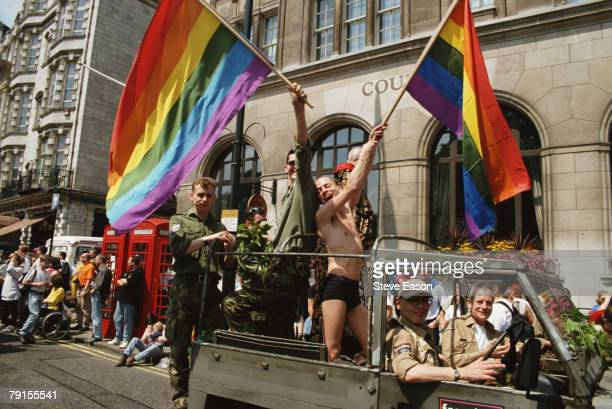Men waving rainbow flags from a jeep during the London Lesbian Gay Bisexual and Transgender Pride event 5th July 1997