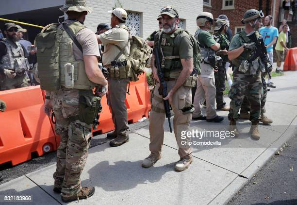 Men wearing body armor combat weapons and patches that read 'New York Militia 'evacuate white nationalists neoNazis and members of the 'altright' who...