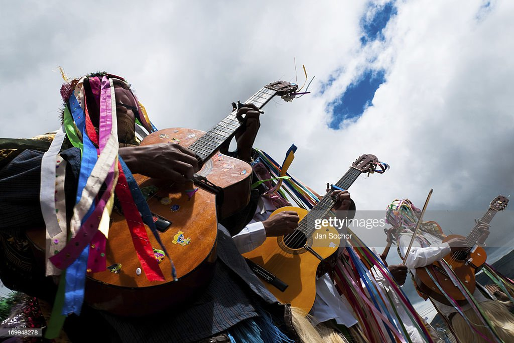 "Men, wearing colorful costumes, play guitars during the Inti Raymi celebration on 26 June 2010 in the village of Pesillo, Ecuador. Inti Raymi, ""Festival of the Sun"" in Quechua language, is an ancient spiritual ceremony held in the Indian regions of the Andes, mainly in Ecuador and Peru. The lively celebration, set by the winter solstice, goes on for various days. The highland Indians, wearing beautiful costumes, dance, drink and sing with no rest. Colorful processions in honor of the God Inti (Sun) pass through the mountain villages giving thanks for the harvest and expressing their deep relation to the Mother Earth (Pachamama)."