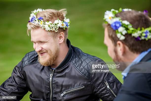 Men wearing flower wreaths