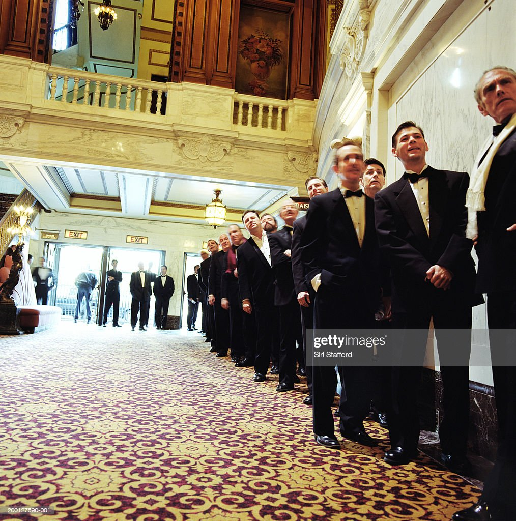 Men wearing formal attire, standing in line of theater lobby : Stock Photo