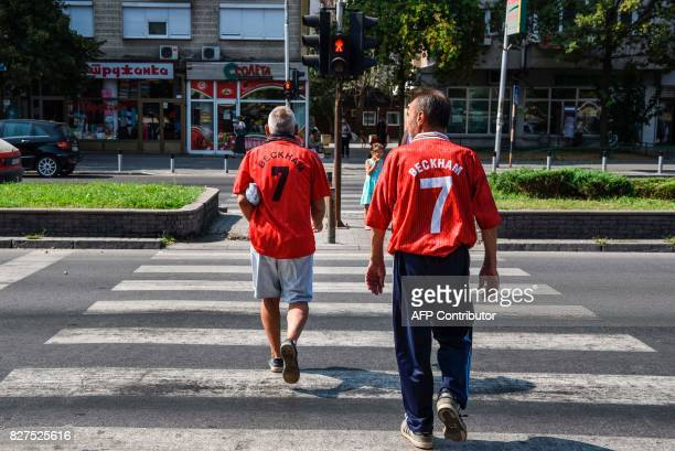 Men wearing old Manchester United jerseys walk in the city of Skopje on August 8 2017 ahead of the UEFA Super Cup football match between Real Madrid...