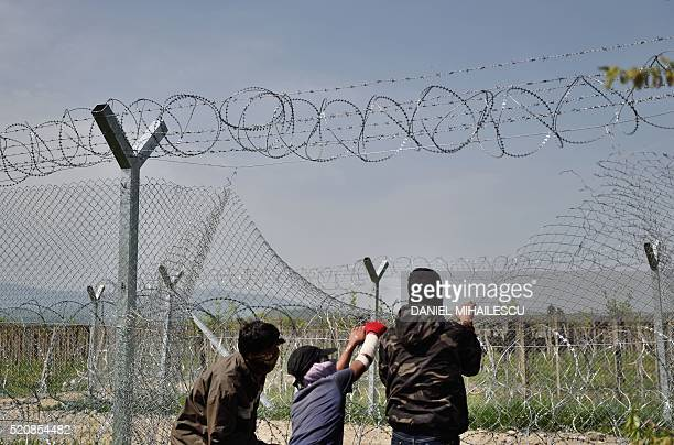 TOPSHOT Men wearing scarves over their mouths try to pull down the border fence between Greece and Macedonia near the Greek village of Idomeni on...