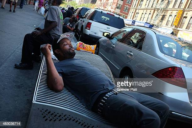Men who are high on K2 or 'Spice' a synthetic marijuana drug sleep along a street in East Harlem on August 5 2015 in New York City New York along...