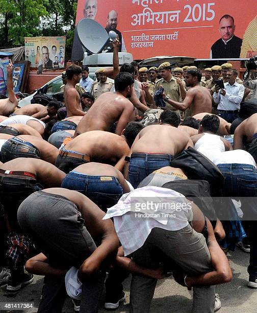 Men who had cleared constable recruitment exam hold a protest by removing their shirts and displaying a pose of corporal punishment demanding...