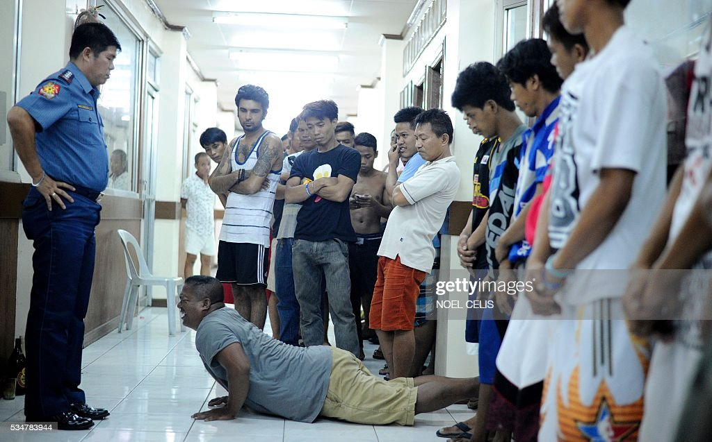 Men who violated the 10pm liquor ban, seen drinking on public places, are temporarily detained and made to do 40 push-ups at a police headquarters in Manila on May 28, 2016. A police station in Manila implemeted Oplan 'RODY,' or Rid the streets Of Drinkers and Youths. President-elect Rodrigo Duterte will impose a nationwide curfew on children being on the streets late at night and is also considering banning the serving of alcohol after midnight, his spokesman Peter Lavina said earlier this month. / AFP / NOEL