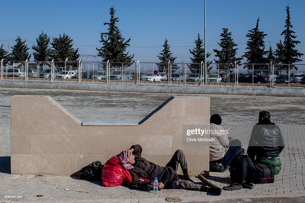 Men wishing to return to Syria wait for transport to arrive as a small number of Syrian refugees were allowed to return to Syria at the closed Turkish border gate on February 9, 2016 in Kilis, Turkey. According to Turkish officials some 35,000 Syrian refugees have massed on the Syrian/Turkish border after fleeing Russian airstrikes and a regime offensive surrounding the city of Aleppo in northern Syria. Turkey's President Recep Tayyip Erdogan said Turkey would open it's doors' if necessary'